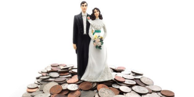 Plastic wedding couple on a pile of coins - money