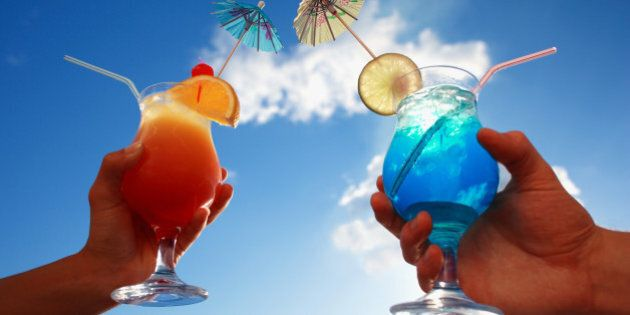 holding tropical cocktails with umbrellas, ice, fruit and straws against a blue sunny sky