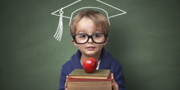 Child holding stack of books with mortar board chalk drawing on blackboard concept for university education...