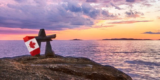 An Inukshuk at sunset holding a Canadian flag overlooking a body of water.