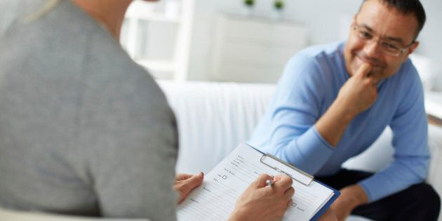 Female psychologist consulting mature man during psychological therapy