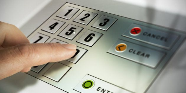Finger about to press a pin code on a pad. Security code on an Automated Teller Machine,