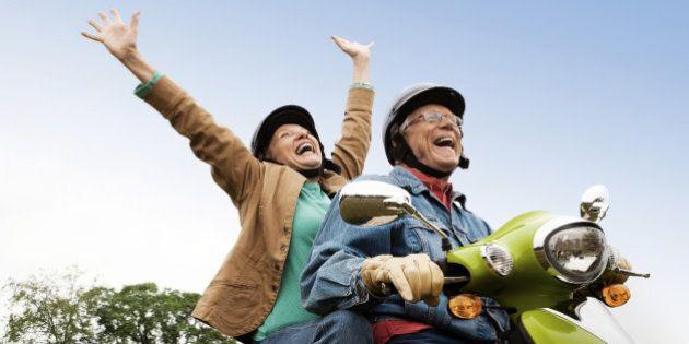 Senior couple having fun riding motor scooter. Horizontal