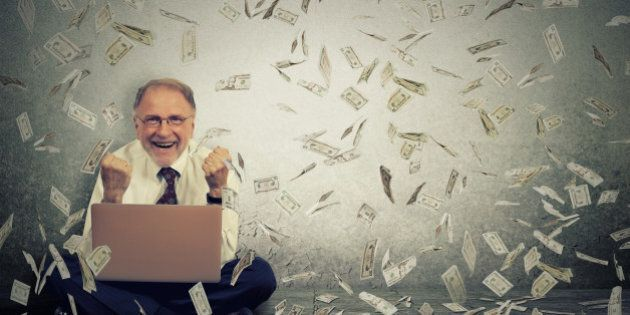 Senior business man using a laptop building online business making money dollar bills cash falling down....