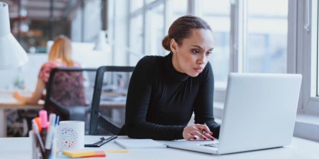 Image of woman using laptop while sitting at her desk. Young african american businesswoman sitting in...