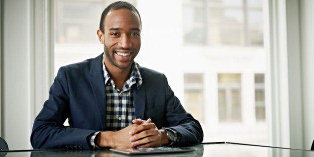 Businessman sitting at office conference room table hands folded smiling digital tablet on