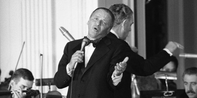 Singer Frank Sinatra belts out a song during an appearance at the White House, Washington, April 18, 1973. Sinatra, who retired from singing last year, returned to the stage for the first time as he sang 10 songs during the evening. He entertained during a state dinner honoring Italy's Prime Minister Giulio Andreotti. Behind Sinatra is bandleader Nelson Riddle. (AP Photo/Jim Palmer)