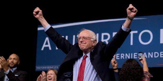 Democratic presidential candidate Sen. Bernie Sanders, I-Vt., center, acknowledges the cheering crowd...