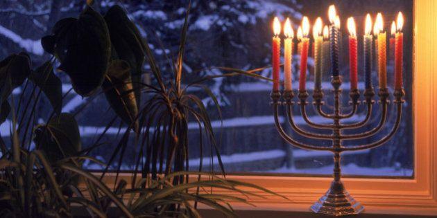 Lit menorah in window during