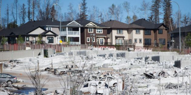 Houses and vehicles destroyed by wildfire are seen in the Timberlea neighborhood of Fort McMurray, Alberta,...