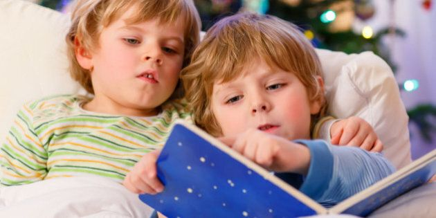 Two little blond sibling boys reading a book in bed near Christmas tree with lights and illumination....