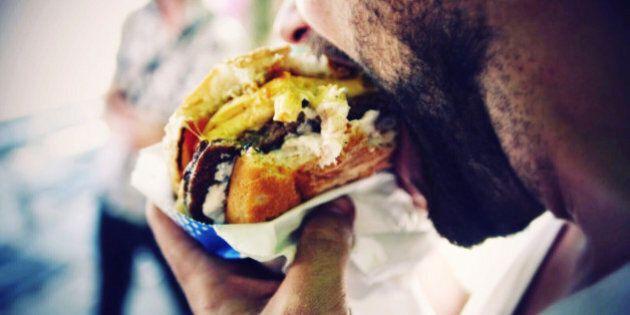Close-Up Of Man Eating Cheeseburger On