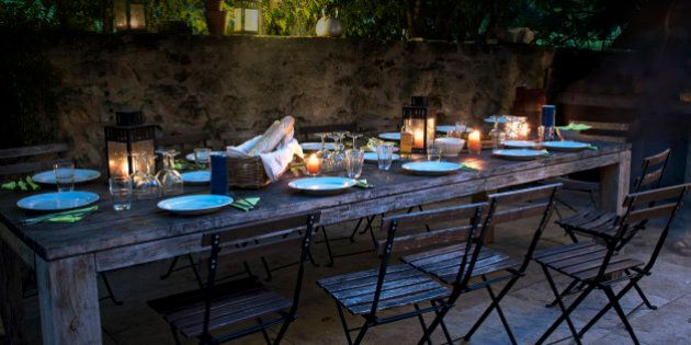 large rustic table on the terrace prepared for a outside dinner with friends from the evening until late...