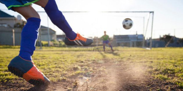 Close up action of boy, aged 14, taking a penalty kick in a football