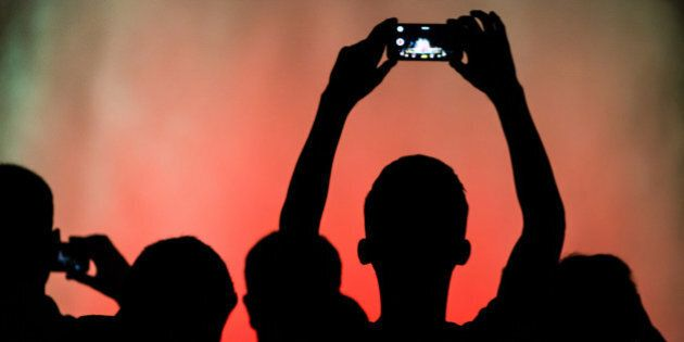 Black silhouettes of people taking pictures with smartphone at dark night in Barcelona city with only...