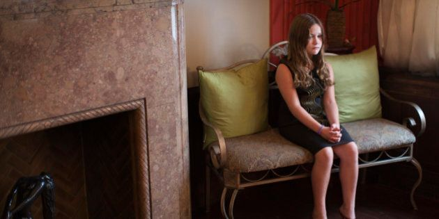 Portrait of unhappy girl sitting on seat in living room