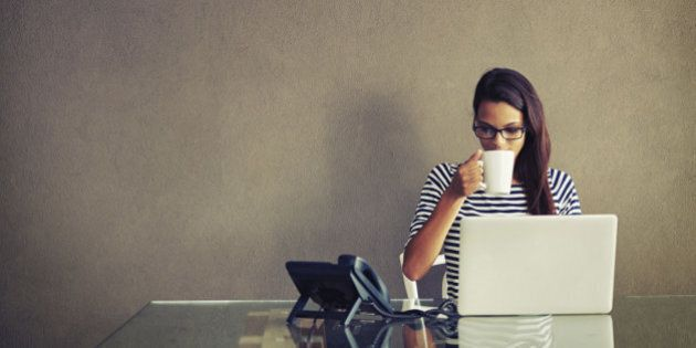 An attractive young businesswoman having coffee while working at her office desk