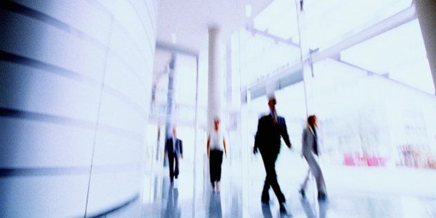 Business people in corridor of office building, (blurred motion)