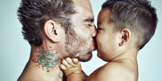 Playful baby boy gets close and makes a scrunchy face to kiss his dad.