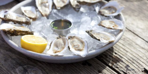 fresh raw oysters served with lemon and sauce at the plate with