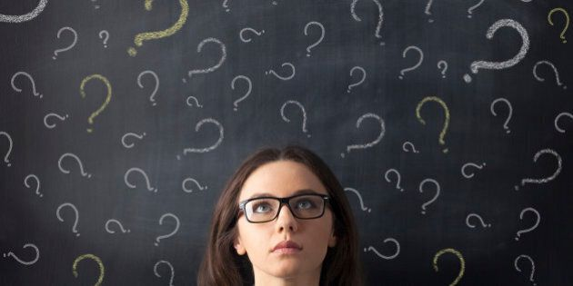 Businesswoman's head is visible surrounded by question marks drawn on a blackboard behind her. The woman...