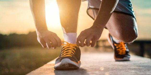 Man tying jogging shoes.A person running outdoors on a sunny day. The person is wearing black running...
