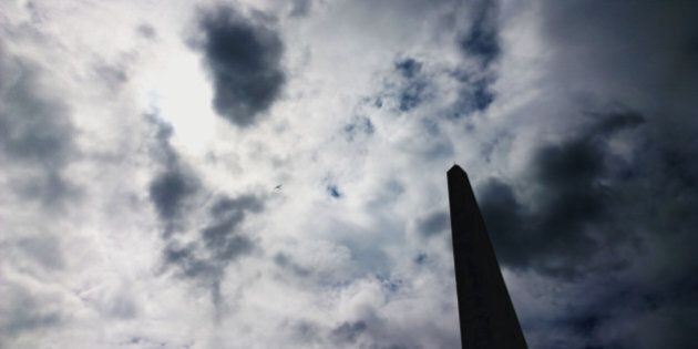 a science fiction type obelisk against a cloud filled