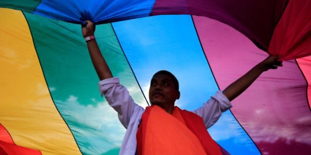 A man displays a rainbow flag during a LGBT Pride parade in metro Manila, Philippines June 25, 2016....