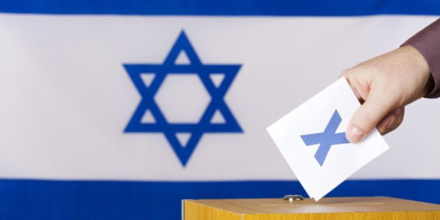 Hand inserting a ballot to ballot box. Flag of Israel in the