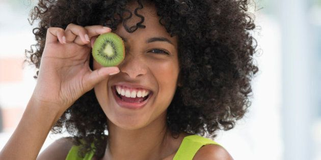 Smiling woman holding a kiwi fruit in front of her