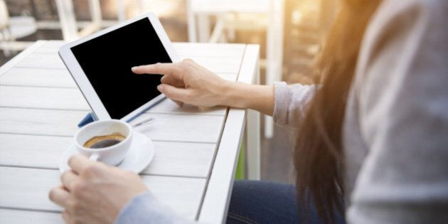 Close up shoot of a young caucasian businesswoman at the cafè during the breakfast using her digital tablet with blank screen and drinking an italian 'espresso' coffee.