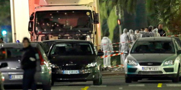 Forensic officers stand near a truck with its windscreen riddled with bullets, that plowed through a...