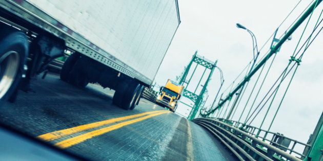 Driving in a speeding car passing two large oncoming semi tractor trailer trucks at the apex of the Thousand...