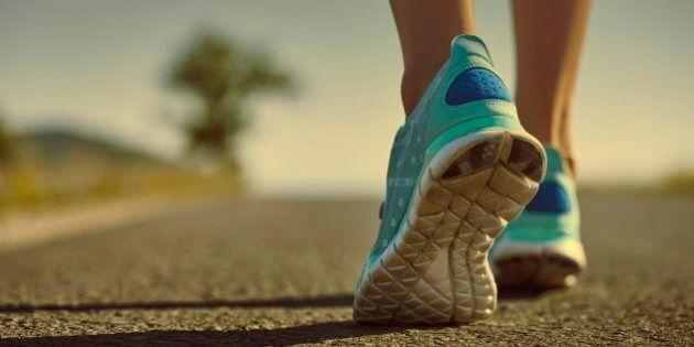 Closeup of athlete female feet in running shoes jogging on the road early in the morning. Healthy lifestyle.