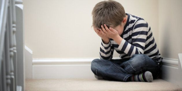 Upset problem child with head in hands sitting on staircase concept for childhood bullying, depression...