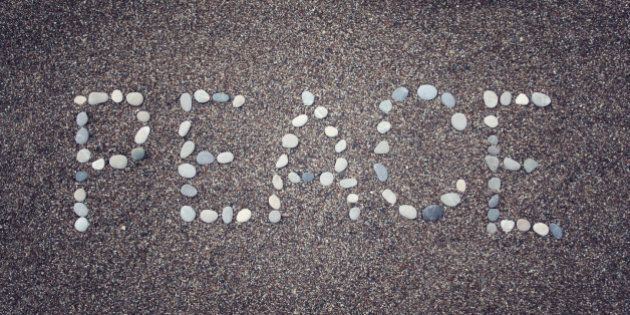 'Peace' word written with pebbles on the sand. Aged photo. 'Peace' word made by small stones on the beach....