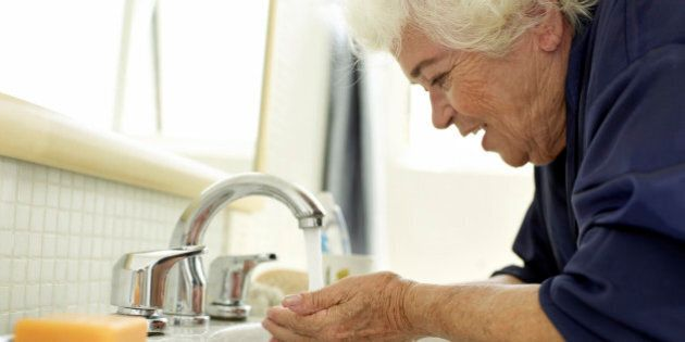Elderly woman washing her face after wake