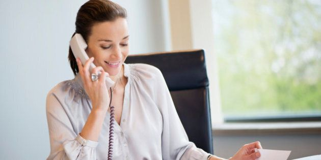 Businesswoman talking on a landline phone in an