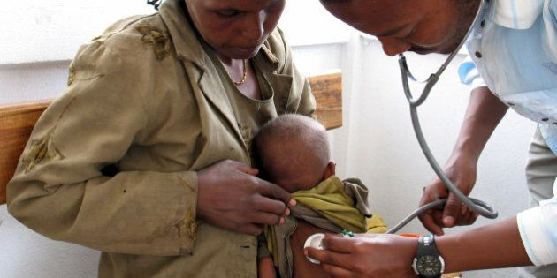 A doctor checks the heartbeat of a malnourished child at a clinic run by the medical charity Doctors...