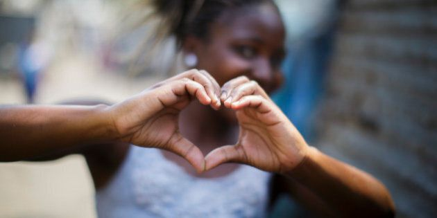 Beira, Mozambique - September 28: A girl formes a heart with her hands in a slum in the city area Beira...