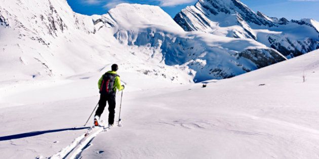 Backcountry skier skinning along a gradual snow slope towards radical looking mountains in Burstall