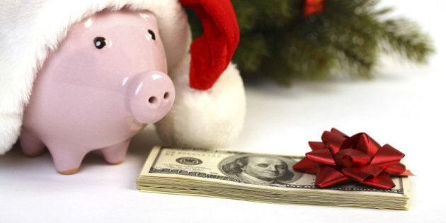 Part of piggy bank with Santa Claus hat and stack of money american hundred dollar bills with red bow...