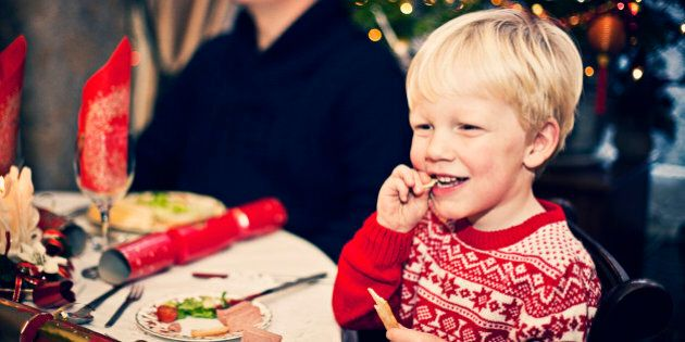 Happy smiling little boy enjoying his Christmas dinner with family.