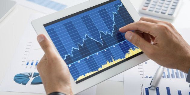 Close Up Of A Businessman Analyzing Graph On Digital