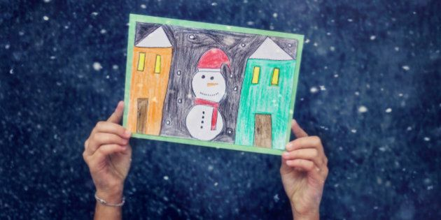 child hands holding a hand made christmas card with snowman and winter houses,Blue , snow