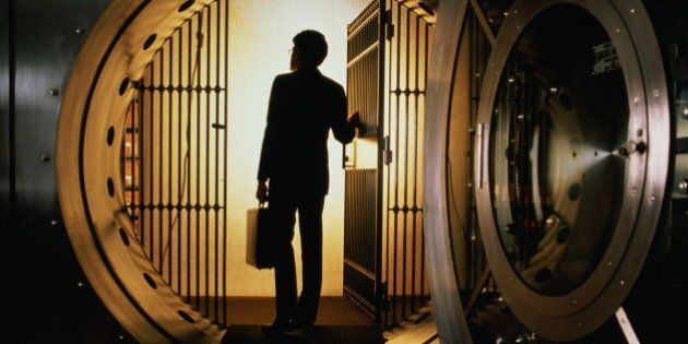 Man with briefcase silhouetted in open door of bank