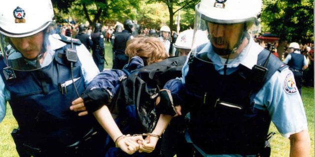 TORONTO, ON - JUNE 15: Anti-poverty protesters threw molotov cocktails, paint bombs and fist-sized chunks of concrete at police in front of the Ontario Legislature yesterday to protest the government's social policies. Hundreds of protesters battled scores of Toronto police in an hour-long skirmish - the worst violence the Legislature has seen - to protest homelessness, the abolition of rent controls and other social policy measures. The trouble began after John Clarke, organizer for the Ontario Coalition Against Poverty (OCAP) which led the march, was denied access to the Legislature to address MPP's. Met with locked doors and lines of police in riot gear Clarke encourage demonstrators to don gas masks and eye shields. June 15, 2000.        (Boris Spremo/Toronto Star via Getty Images)