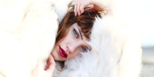 A model in a white fur coat poses during a photo shoot on a