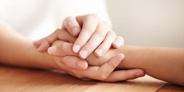 Hands holding one another on a table in