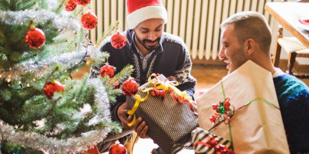 Gay interracial couple exchanging gifts under the christmas tree